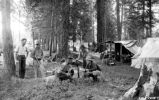 Unidentified group of campers (men) with Ranger reading from book