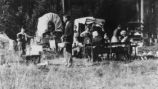 1913 wagon trip, Camp at Mill Creek Station, shows wagons, table and kitchen area